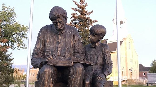 Une sculpture d'un homme qui lit un livre. Assis à sa gauche est un jeune garçon qui regarde le livre.