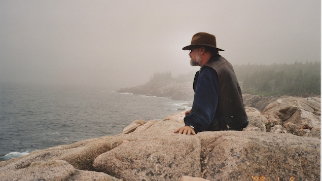 L'homme est assis sur les rochers et regarde au loin.