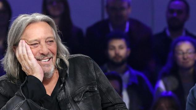 Le musicien sourit dans un studio de télé. Des membres du public sont situés derrière lui.
