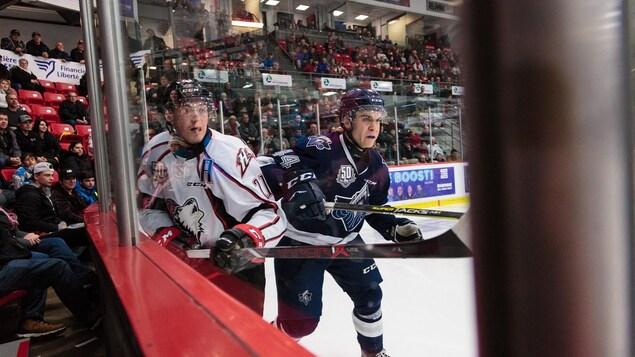 Deux joueurs de hockey lors d'une mise en échec contre la bande.