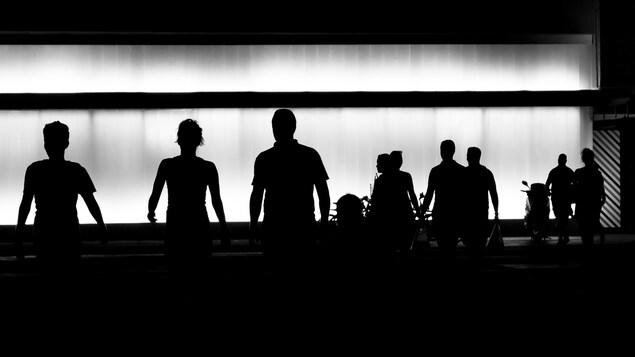 Image en noir et blanc montrant des silhouettes de personnes marchant dans une rue.