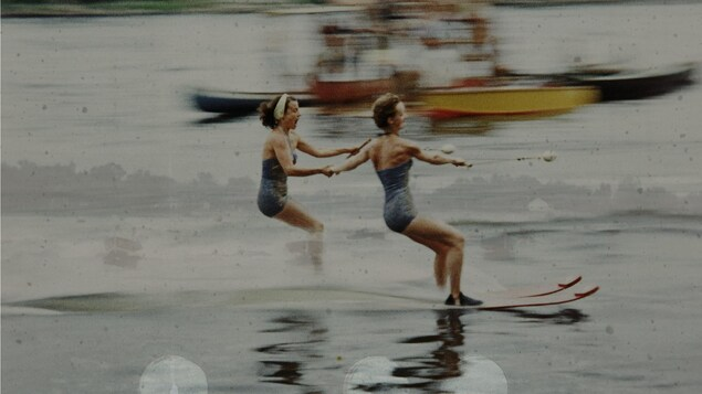 """Deux femmes font du ski nautique en se tenant la main sur la rivière des Mille-Îles. Photogramme 16mm altéré transféré en numérique tiré du film documentaire """"Au pays des Mille-Îles"""" de Lisa Sfriso."""