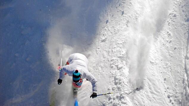 Vue aérienne d'une skieuse vêtue de blanc.