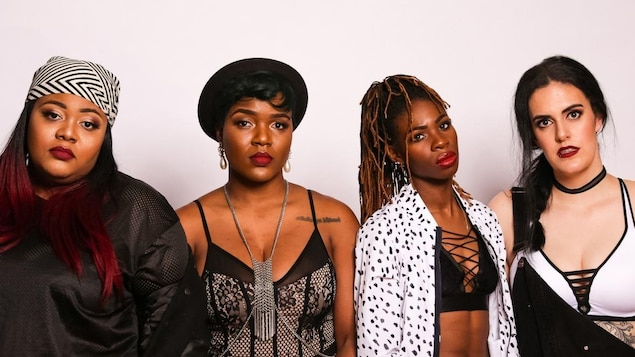 Les quatre femmes du collectif rap The Sorority devant un mur blanc.