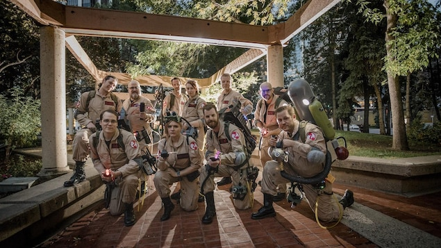 10 membres du groupe Alberta Ghosbusters posent habillés de leur costume de chasseurs de fantômes.