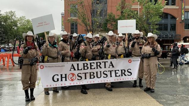 Dix membres déguisés en chasseur de fantômes prennent part au défilé du Stampede à Calgary sous la pluie.