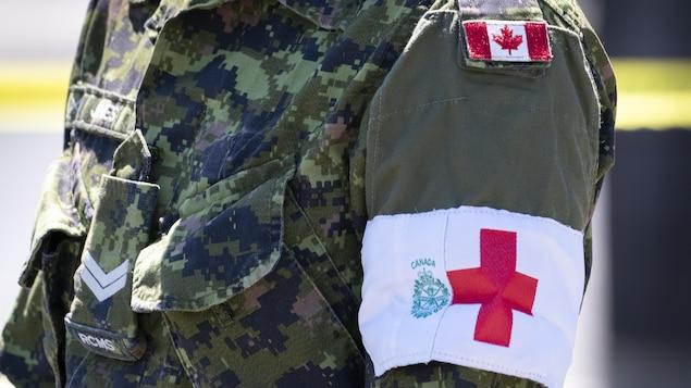 Un militar con un brazalete médico.