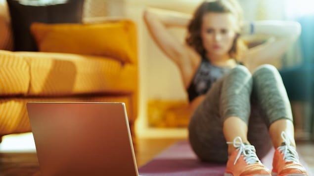 Une femme fait des abdos sur un tapis de yoga dans son salon en regardant un écran d'ordinateur.