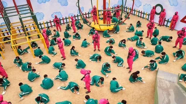 Des personnes habillées en vert sont accroupies sur le sol, menacées par d'autres personnes habillées en vert et munies de fusils.