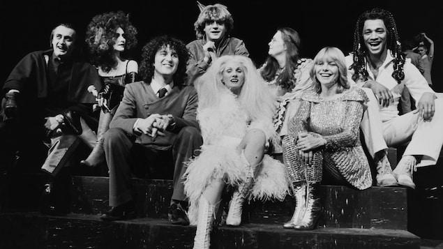 Image de scène en noir et blanc avec les interprètes en costumes.