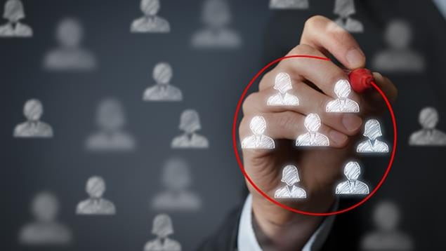 Gros plan sur une main qui entoure au marqueur un groupe de personnes dessinées.