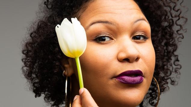 Une femme tient une tulipe blanche devant son visage.
