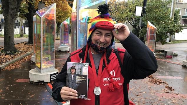Stéphane Scott tient dans sa main son agenda Hope in Shadows 2021. Il a le manteau rouge des vendeurs Megaphone, une médaille au coup et un chapeau multicolore.
