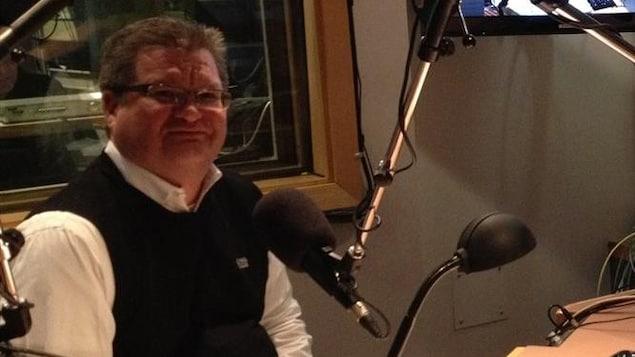 Plan moyen de Stéphane Dorge assis dans un studio radio.
