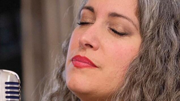L'artiste chante une mélode les yeux fermés.