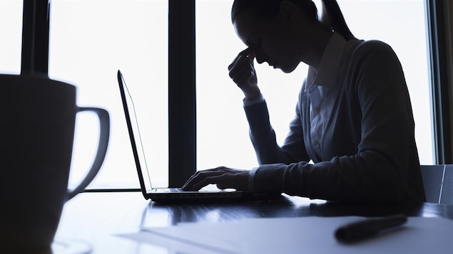 Les yeux fermées et exténuée, une travailleuse prend une pause devant son ordinaire portable.