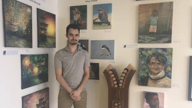 Un homme est debout devant des oeuvres d'art dans une galerie.