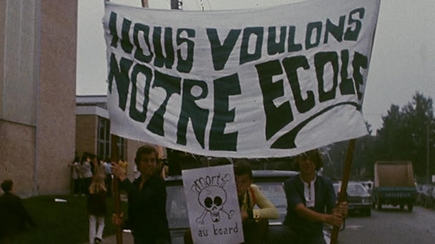 Des adolescents tiennent une grande bannière sur laquelle on peut lire « Nous voulons notre école ».