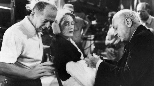 Le réalisateur d'origine autrichienne Billy Wilder (à gauche) et le réalisateur américain Cecil B. DeMille se tiennent de chaque côté de l'acteur américain Gloria Swanson sur le tournage du film Sunset Boulevard, en 1950.