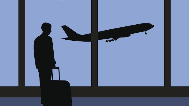 Un homme regarde un avion décollé.