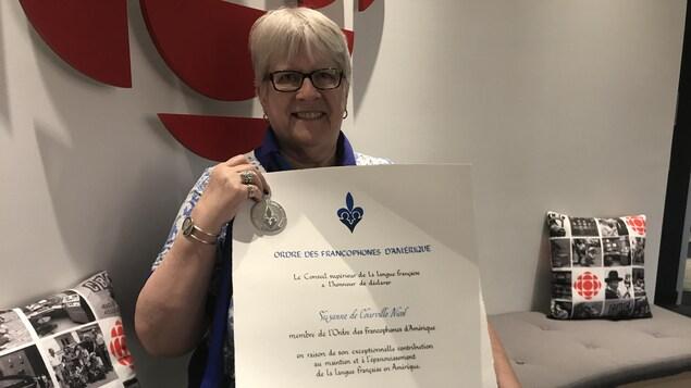 Une femme tient un document officiel devant un logo de Radio-Canada.