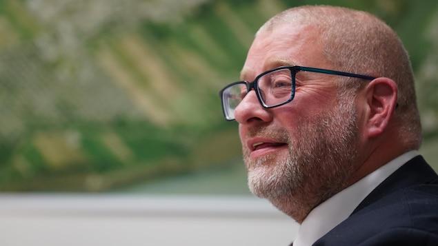 Le maire de Saint-Augustin-de-Desmaures, Sylvain Juneau, devant la carte de sa ville, avec des lunettes et une barbe de trois jours.