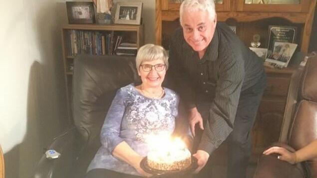 Un couple dans leur salon avec un gâteau allumé de bougies.