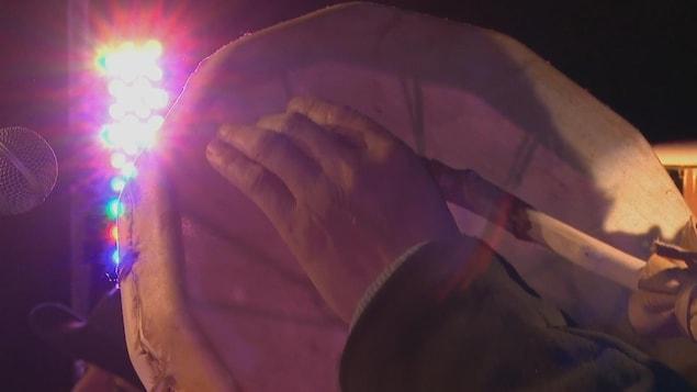 Une main tient un tambour.