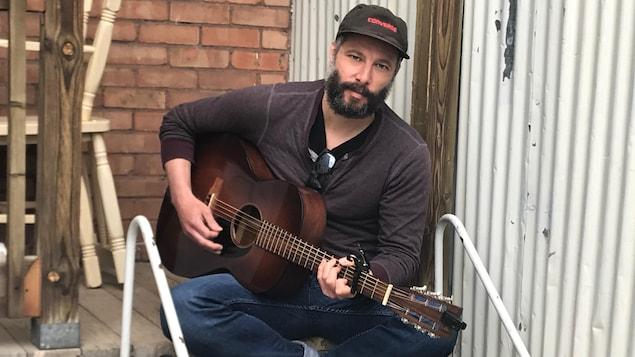 L'auteur-compositeur-interprète Tire le coyote est assis sur les marches d'un escalier avec sa guitare.