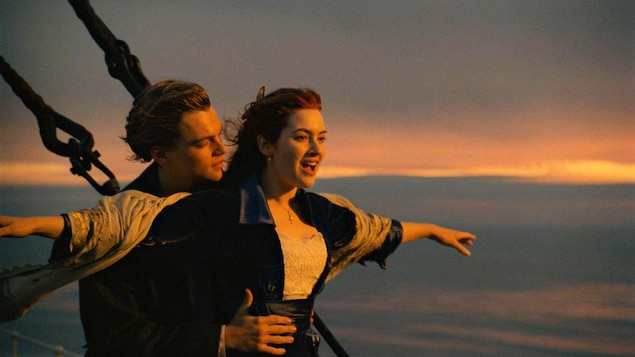 Un homme et une femme sont sur un navire. La femme étend les bras sur les côtés, l'homme la tient par la taille.