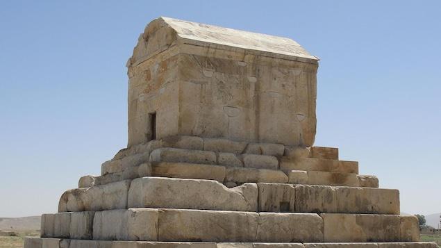 Un petit monument de pierre grimpé sur des marches de pierre.