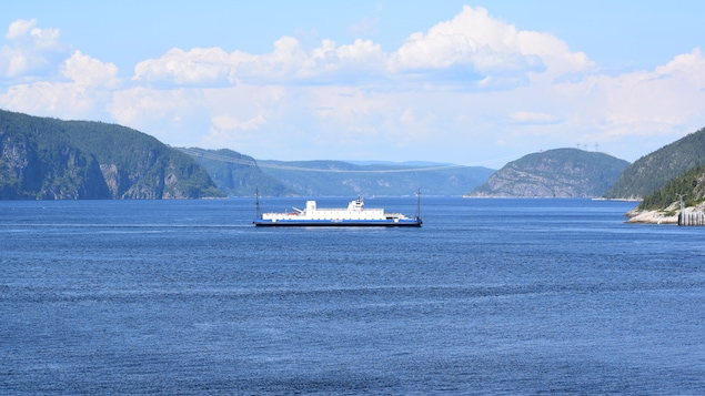 Le projet Énergie Saguenay augmentera le trafic maritime commercial dans le parc marin du Saguenay-Saint-Laurent. On aperçoit le traversier dans le fjord.