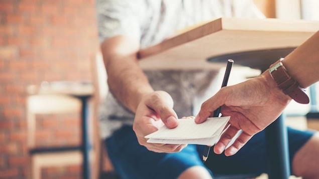 Un jeune homme assis à un bureau dans une classe passe un papier plié à un collègue.