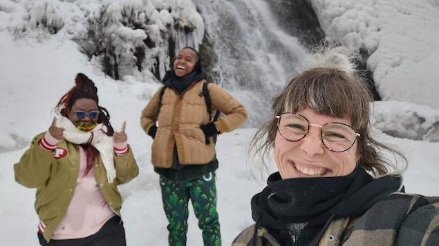 Égoportrait de trois femmes devant une chute dans un décor enneigé.