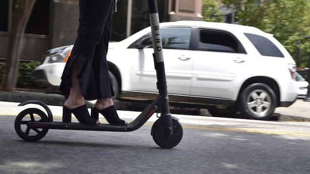 Une femme portant des chaussures à talons conduit une trottinette électrique dans une rue.