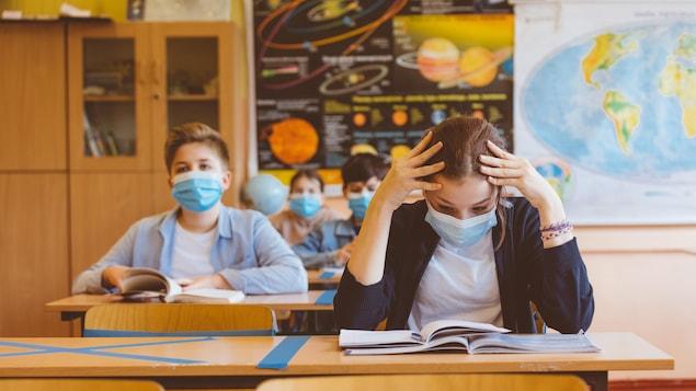 Des élèves du secondaire dans une classe. Une adolescente à l'avant-plan semble préoccupée.