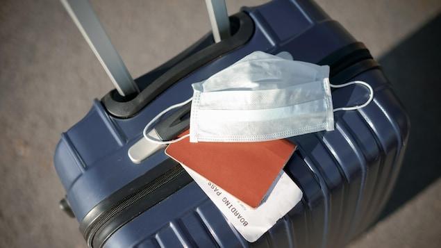 Un masque sur la valise d'un voyageur à l'aéroport.