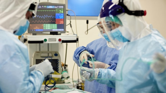 Médecins et infirmières portant des blouses chirurgicales, des lunettes et des masques se préparent à une intervention.