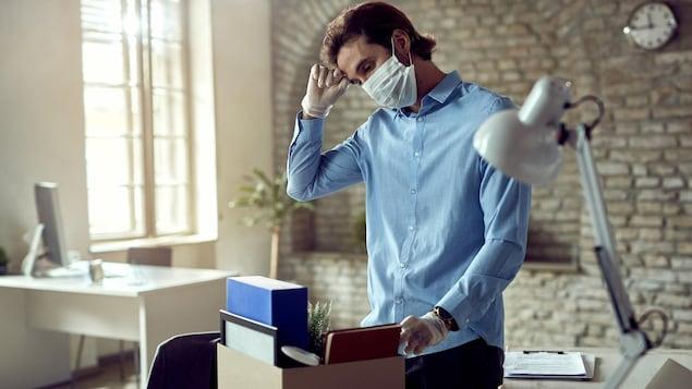 Un homme range ses effets personnels dans une boîte après avoir perdu son emploi en raison de la pandémie de COVID-19.