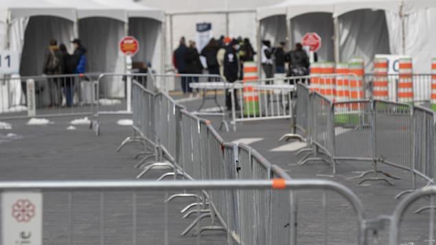 Des barrières de métal et quelques personnes, en arrière-plan, près des tentes blanches installées par la Ville de Montréal.