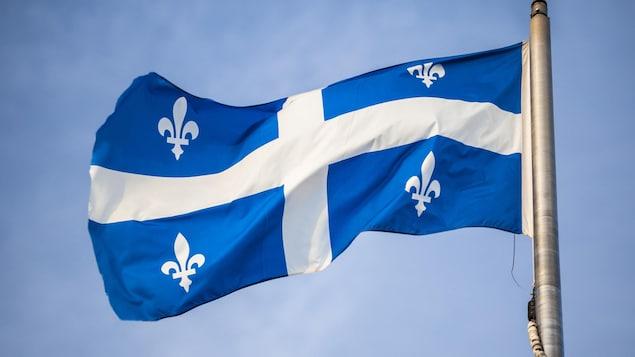 Le drapeau fleurdelisé, sur un mat, flotte au vent.