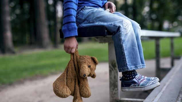 Un enfant est assis dans des estrades avec son toutou.