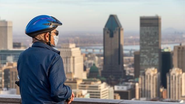 Sur le belvédère du mont Royal, un homme qui porte un casque de vélo et un masque regarde à l'horizon.