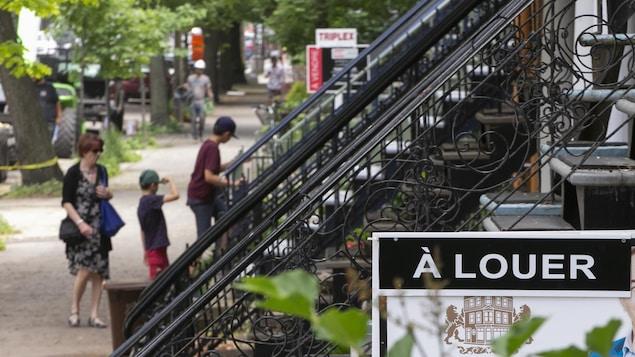 Une femme et deux enfants montent un escalier derrière une pancarte de logement à louer.