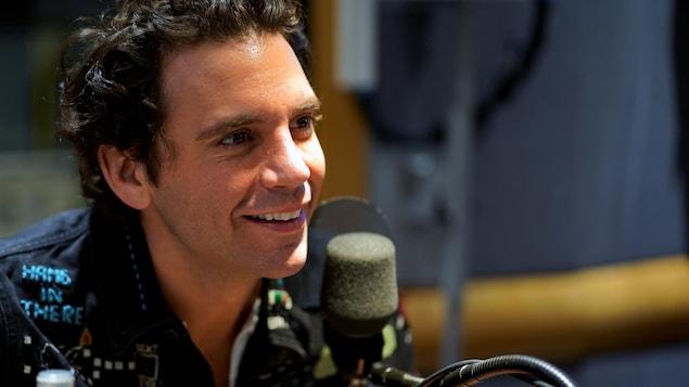 Le chanteur Mika, souriant, devant un micro de radio.