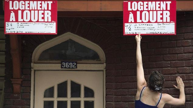 Une femme retire une pancarte « logement à louer » sur un immeuble.