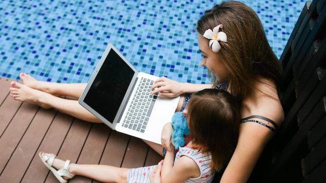 Une femme sur son ordinateur, près de la piscine.