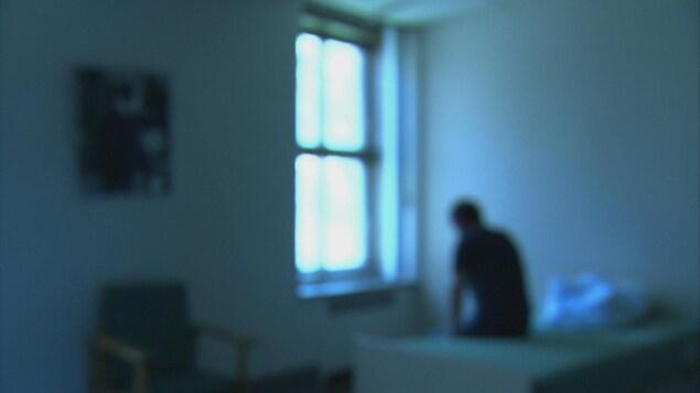 Une image floue d'un homme assis sur un lit dans une petite chambre d'hopital.
