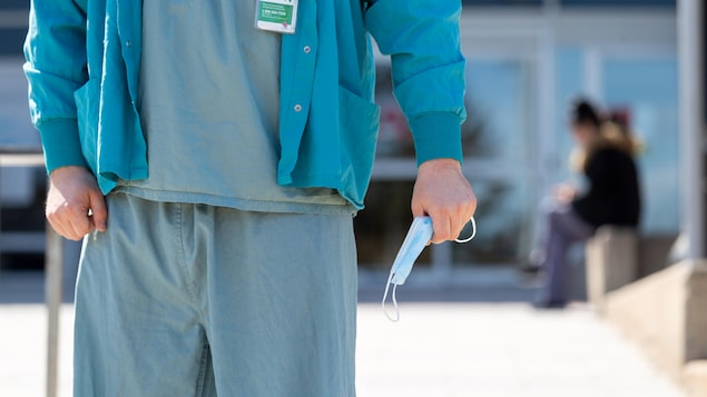 Un travailleur de la santé tient un masque dans sa main.
