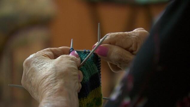 Plan rapproché sur des mains d'une personne âgée en train de tricoter. Quatre crochets de tricot permettent de tricoter la laine.